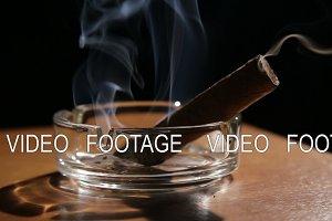Smoking cigar in an ashtray.