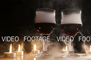Wine glasses and burning candles in