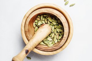 Dried cardamom in wooden bowl with p