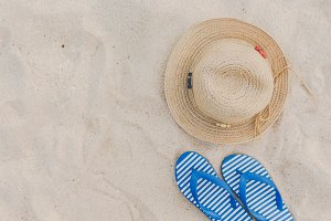 Straw hat and flip flops on beach