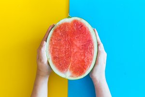 Hand holding watermelon on colourful