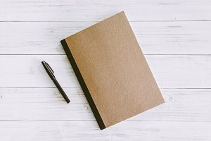 Note book and pen on wooden