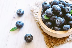 Blueberries in wooden bowl on wooden