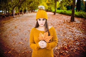 Beautiful young woman holding a leaf