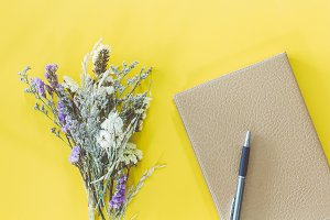 Notebook and dried statice flowers