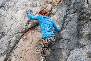 Young girl climbing up the rock in T