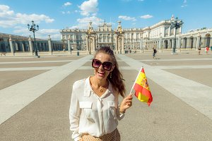 smiling tourist woman with Spain fla