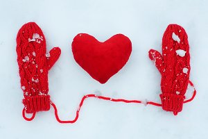 Red mittens and plush heart on snow