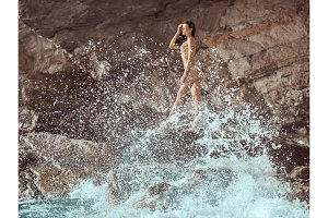 Beautiful young woman on wild rocky