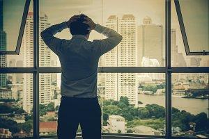 Depressed man standing head in hands