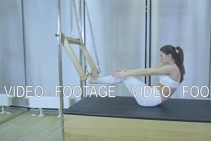 Pilates. Woman in white clothes