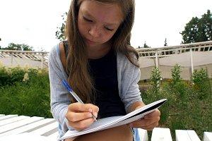 Girl writes music on sheet sitting