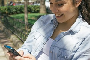 Woman using her phone smiling