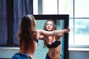 Sexy young woman looking in mirror