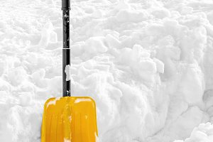 Yellow plastic shovel stuck in snow