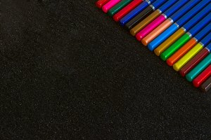 A rainbow of colored pencils, on a dark background.