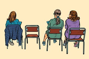 women sit back on chairs