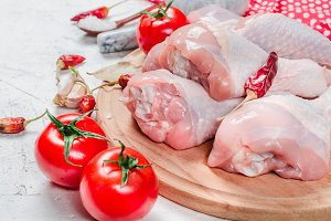 Raw chicken legs on cutting board wi