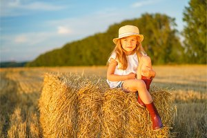 Little girl in a field with hay