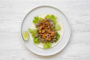 Shrimp taco with lime on round plate