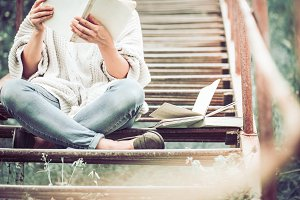 girl reads a book on the steps