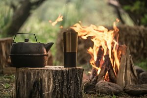 camping items by the fire kettle wit