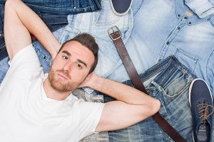 man lying on many jean clothes