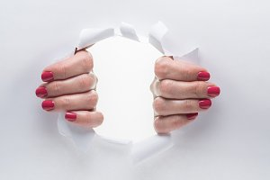 Woman's hands tearing the hole on a