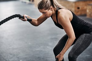 Fit woman working out with ropes dur