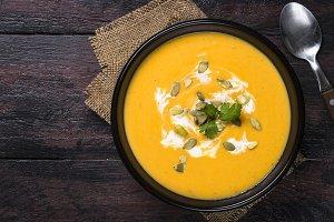 Pumpkin cream soup on dark wooden