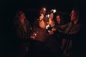 Group of friends lighting fire spark
