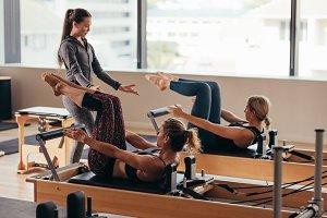 Pilates trainer instructing women