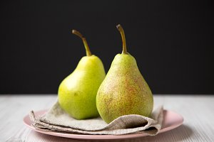 Tasty fresh pears on pink plate