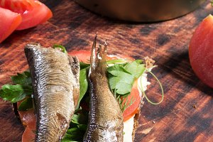 Fresh tomatoes and sprats. Greens an