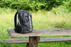 Backpack on wooden table outdoors