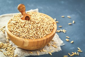Raw grain of oats in a wooden bowl a
