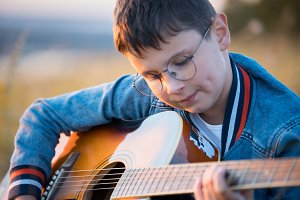 Young teen boy playing acoustic