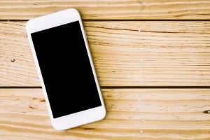 Blank screen smartphone on wooden