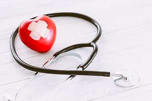 Stethoscope with red heart on wooden