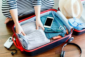 Woman packing a luggage on wooden