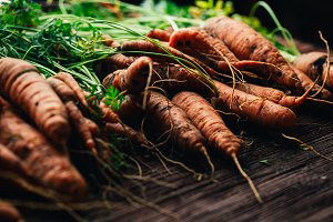 Fresh carrots close-up on a wooden b