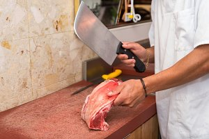 butcher cutting steaks