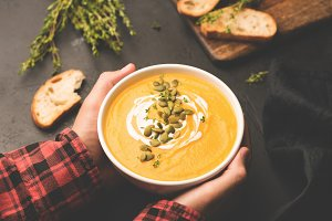 Person holding bowl of pumpkin soup