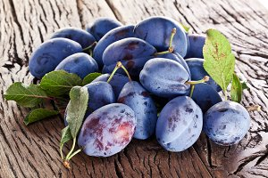 Plums on an old wooden table.