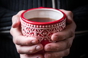 Hands holding red mug