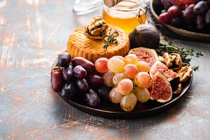 Cheese plate served with grapes, jam