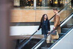 A young couple on an escalator in
