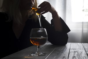 Woman drinking alcohol alone looking