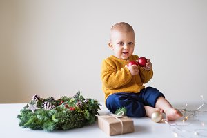 A toddler boy and a christmas wreath