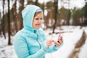 Senior woman runner with smartphone
